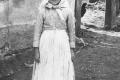 Helena Ďatková od Bačkaďov, slobodné dievča má na sebe čižmy s tvrdou sárou, blúzku s dlhým rukávom, sukňu a bielu zásteru – novší kroj zo 40-tych rokov