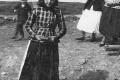 Ženy idú z kostola- Emília Gajdošová Šándorová má oblečenú lipiťku, bielu sukňu a glotovú zásteru, poltopánky s prackou – tieto topánky boli novota a ženy si ich veľmi šanuvali